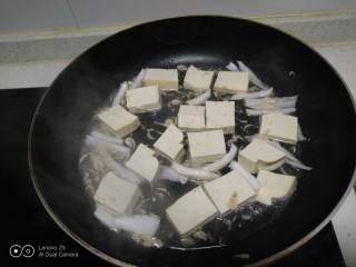 虾米豆腐炒菠菜,不粘锅中放入少许油,放入葱丝炒香虾米,放入豆腐,加入一点水。