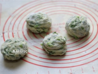小白菜饼,将小剂子旋转着拧几圈,再用手掌压扁,制成饼胚。