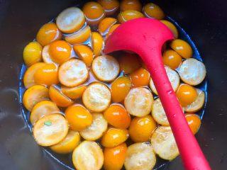 金桔酱,待冰糖完全融化,倒入切好的金桔,大火煮至水开。