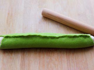 翡翠白玉生煎包,然后把绿色面皮包住白色长条,把边边用手捏紧。