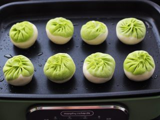 翡翠白玉生煎包,锅中用刷子蘸少许食用油,涂抹一下锅底,锅热后放入包子。