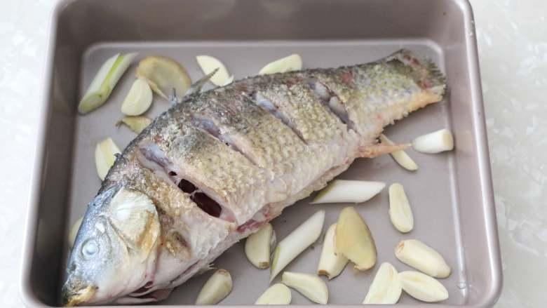 香辣烤鱼,烤盘底部铺上蒜瓣、姜片、葱段,将煎好的鱼放入烤盘中。