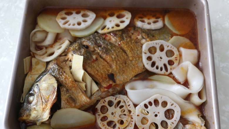 香辣烤鱼,将焯烫好的配菜放入烤盘中。