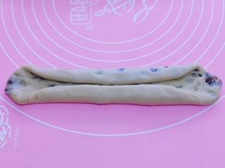 红豆日式咖啡面包卷,取一块面团,用擀面杖擀长舌状。