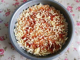 大米披薩,取一部分馬蘇里拉芝士撒上刷了番茄醬的米飯上,大約70克左右,