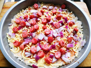 大米披薩,把切好的洋蔥撒在披薩上,再把寶寶腸丁也撒上去,撒的時候注意均勻點