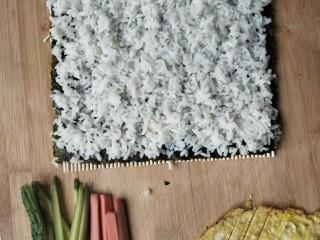寿司,米饭铺在海苔上,适量就行,太少寿司不饱满,米饭上抹匀沙拉酱,黄瓜,火腿,鸡蛋,肉松,放在一堆,海苔从里像外卷起来