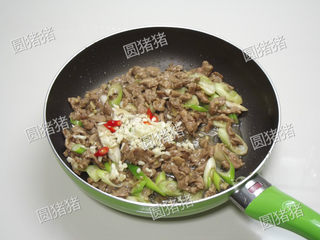 葱爆羊肉,继续大火爆炒约30秒,加入蒜碎及红椒片。