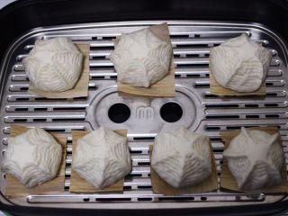 养胃营养的豆沙花样包,蒸锅里加入适量的清水,把做好的豆沙包放到蒸屉上,豆沙包底下垫上玉米叶,开始二发,看见豆沙包发至原来的1倍大的时候。