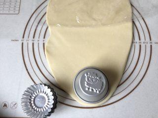 可爱圣诞帽子塔,将面团擀成长方形薄片,取一个圆形模具,刻出圆形面片,圆形模具要比蛋挞模具稍大一点