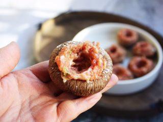 """香菇酿鸡汁肉靡鹌鹑蛋,用筷子夹约13g左右的肉馅将香菇""""杯子""""填满,然后用筷子在中间挖一个洞眼,洞眼的大小和鹌鹑蛋大小差不多。"""
