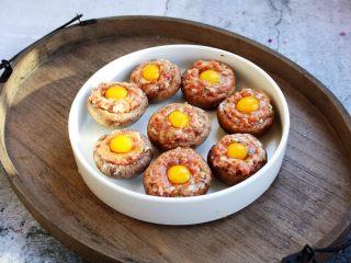 香菇酿鸡汁肉靡鹌鹑蛋,将填满肉馅的香菇放在一个平盘子里,在每个酿好肉馅的香菇上磕入一个鹌鹑蛋。
