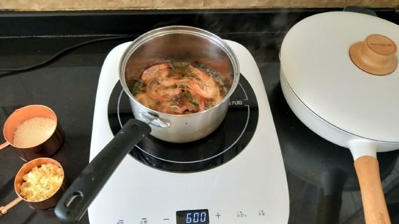 避风塘炒虾,奶锅烧热后放适量油。待油温七八成热,把虾放入,炸到变色后捞出。