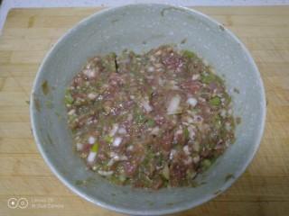 可可味猪肉芹菜饺子,待面醒好,再把芹菜碎放入碗中,用手抓拌均匀。