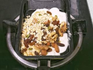 果仁燕麦能量棒,倒入果仁燕麦混合物,用铲子翻拌均匀。