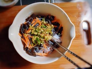 凉拌木耳胡萝卜粉丝,将调好的料汁,倒入装有黑木耳、胡萝卜和粉丝的碗里。