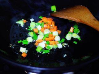 海虹蒜苗什锦蛋炒饭,另起锅倒入剩下的30克花生油烧热后,先爆香蒜苗和胡萝卜丁。