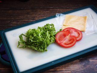三明治,生菜切丝,切两片番茄片,番茄片切的稍稍薄些,芝士片从冰箱冷藏室拿出来,将包装轻轻撕开。