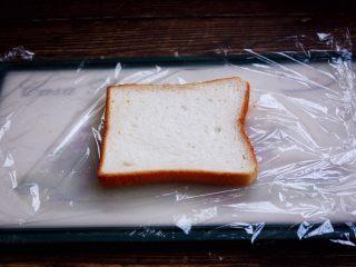 三明治,做三明治时先在粘板上铺上一大块保鲜膜,然后放上一片吐司面包。