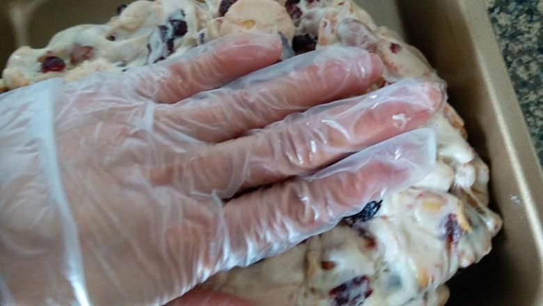 网红雪花酥,稍微冷却后,手上戴手套,两只手拿着糖团不断外翻,使每块饼干都均匀的裹上糖再放入不沾烤盘内,用手按平