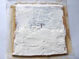 枣泥奶冻蛋糕卷,冰箱取出淡奶油,取一小部分装入裱花袋,留作表面装饰用,剩下的淡奶油抹在凉透的蛋糕表层