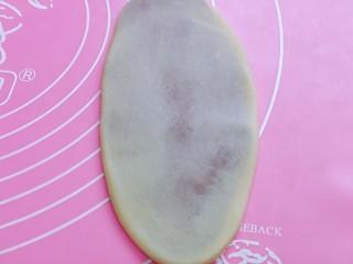 中式甜点~蜜豆桃花酥,取一块面团,收口面朝下,用擀面杖擀成牛舌状,如图。