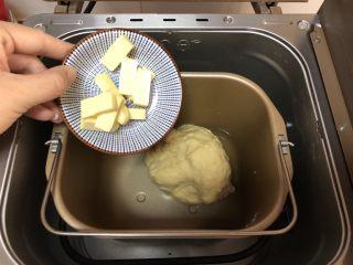 超简易吐司,将室温软化的黄油切小块放入面包机中继续揉面25分钟