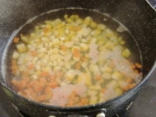 玉米碗蒸,锅里的水烧开后放入玉米和胡萝卜煮三分钟左右,捞起沥干水分