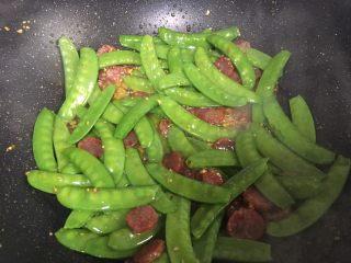 腊肠炒荷兰豆,加入荷兰豆搅拌,然后加少许盐翻炒