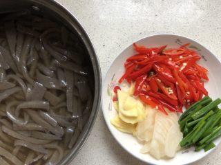 泡椒魔芋丝,魔芋豆腐先切成薄片、再切成细丝。 泡姜和萝卜切薄片、泡椒切丝。