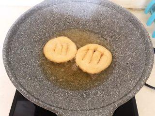 炸油饼,饼坯定型后要不停翻动,让饼坯受热均匀