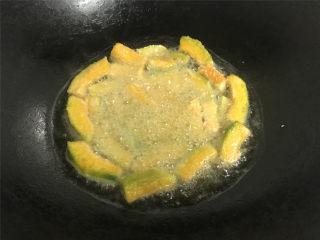 咸蛋黄焗南瓜,锅中倒入适量的油,把裹上淀粉的南瓜条放入锅中,炸至表面呈金黄色后捞出。