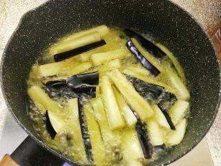 咸鱼茄子煲,一家人抢饭吃的一道菜,中火,倒油把茄子用中火油炸。