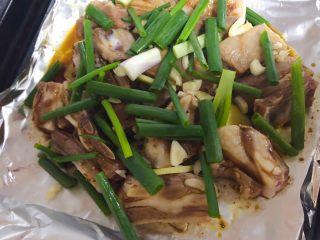 香嫩羊寸排,在烤盘上铺上锡纸,摆好羊寸排,用小勺淋上酱料,姜葱蒜均匀撒在羊排上。