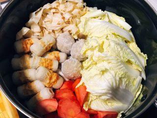 韩式部队锅,将胡萝卜滚刀切块,与娃娃菜、竹轮、沥干的豆皮丝一起平铺在锅里。