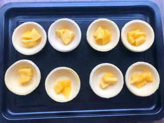 芒果酥,把蛋挞皮一个一个放入盘子里,把芒果块放入蛋挞皮里。