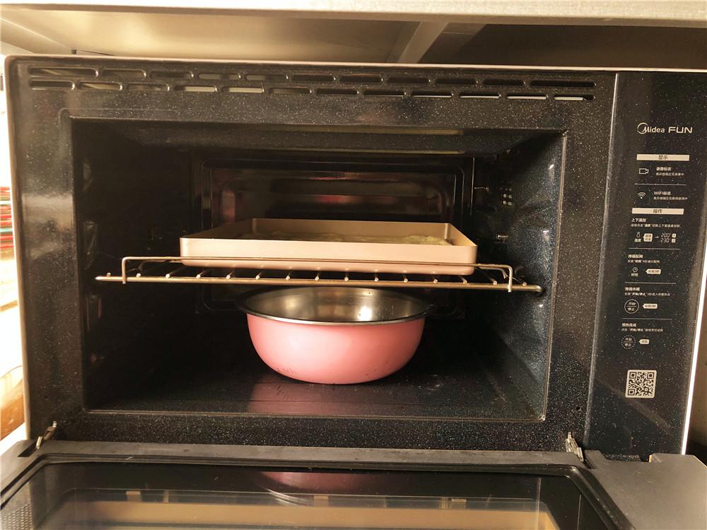 香葱肉松面包卷,把烤盘放到烤箱里,下方放一盆热水二次发酵。一般温度在35度-40度之间,二次发酵时间约30-40分钟。</p> <p>