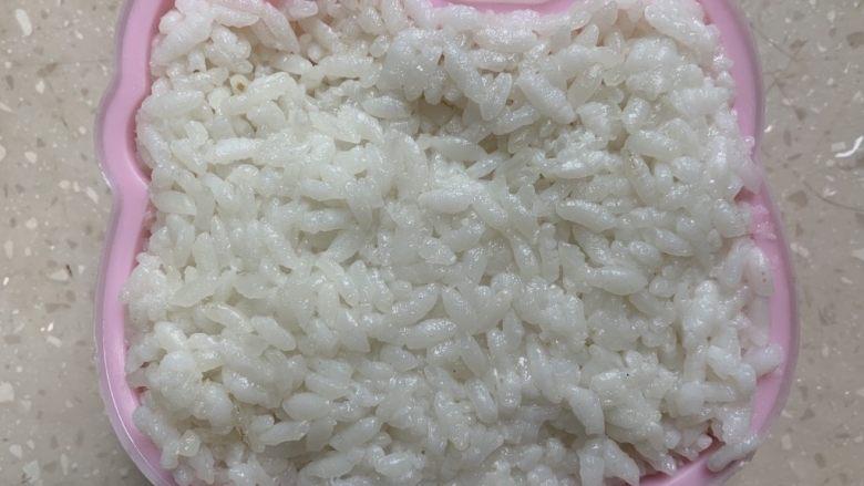 面线虾烤肠彩蔬便当盒,米饭装入模具压紧。
