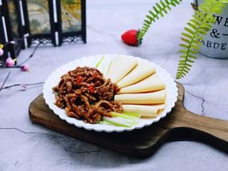 干豆腐皮~京酱肉丝,盛入摆放好的京葱和干豆腐皮盘中,撒上熟白芝麻。