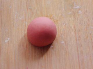 萌猪报春花样馒头,把其中一块红色的面团用手揉圆。