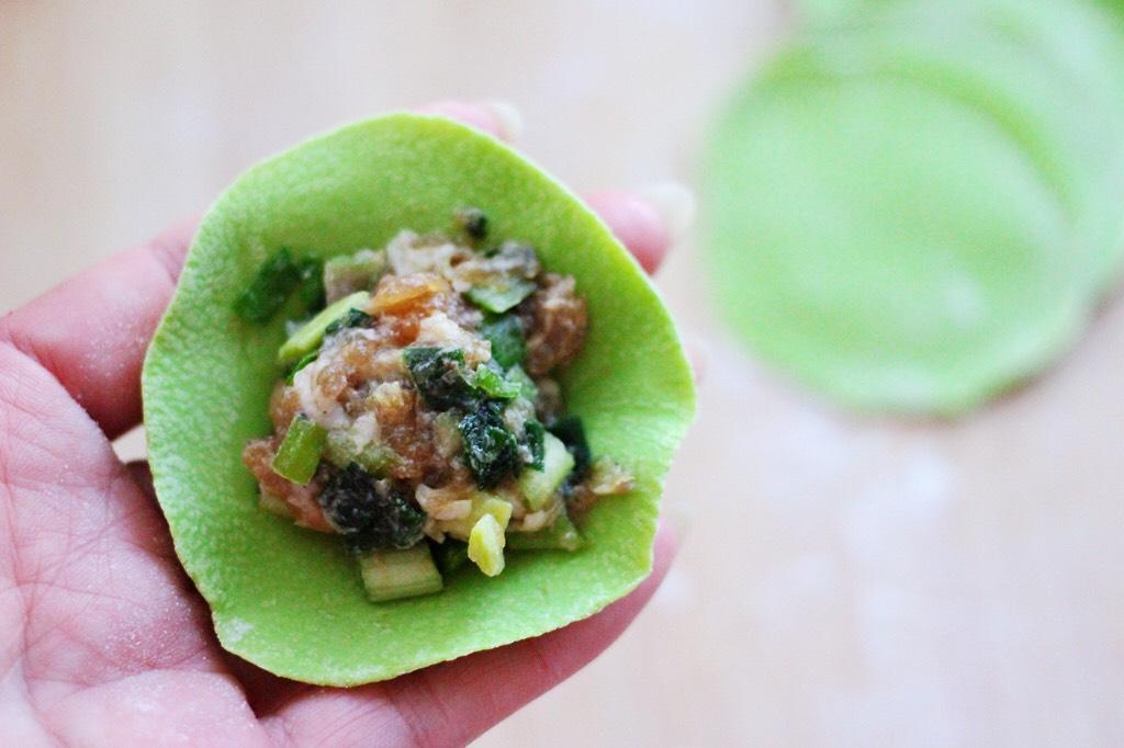 翠玉猪肉韭菜饺子,擀好的面皮里放入适量的馅料。</p> <p>