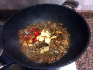 芋儿鸡,放入泡椒、泡姜和大蒜片翻炒20秒。