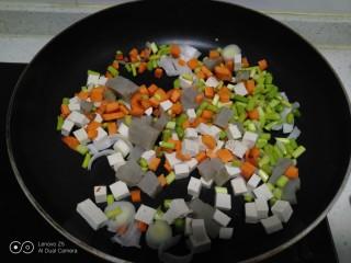 豆腐皮扎排骨炒米,倒入胡萝卜、皮扎、蒜苔、豆腐。