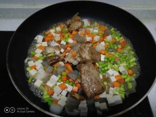 豆腐皮扎排骨炒米,倒入排骨和1勺排骨汤。