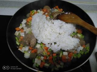 豆腐皮扎排骨炒米,炒至蒜苔、胡萝卜断生,倒入大米。