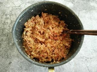 酸菜猪肉饺子,倒入提前剁好的酸菜 继续顺时针搅拌均匀。