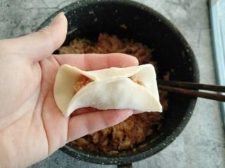 酸菜猪肉饺子,取一小部分饺子馅放饺子皮中间 饺子皮对折 从一端捏出褶子捏紧。