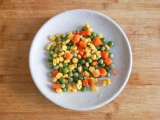 八宝百财福袋,胡萝卜去皮切小丁后和青豆,甜玉米粒一起过水焯一下。