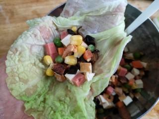 八宝百财福袋,将烫软沥水的白菜叶铺在手心里,用勺子将蔬菜丁放在白菜叶的中间。