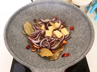 家常红烧牛腩面,加入葱丝和姜片,炒出香味